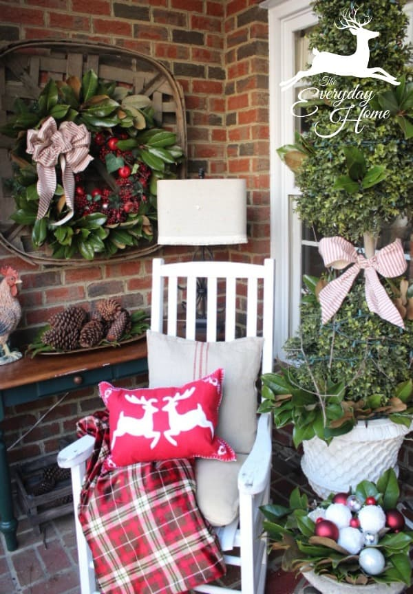 Farmhouse Christmas Decor - a front entry with a christmas tree, rocking chair and lots of red decor