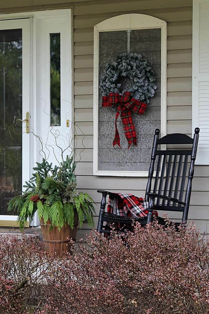 Farmhouse Christmas decor front porch with a rocking chair and a christmas planter