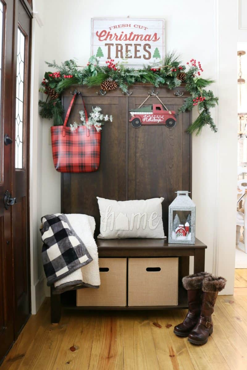 Farmhouse christmas decor front entry with a plaid bag, red truck with christmas tree, garland and christmas trees sign