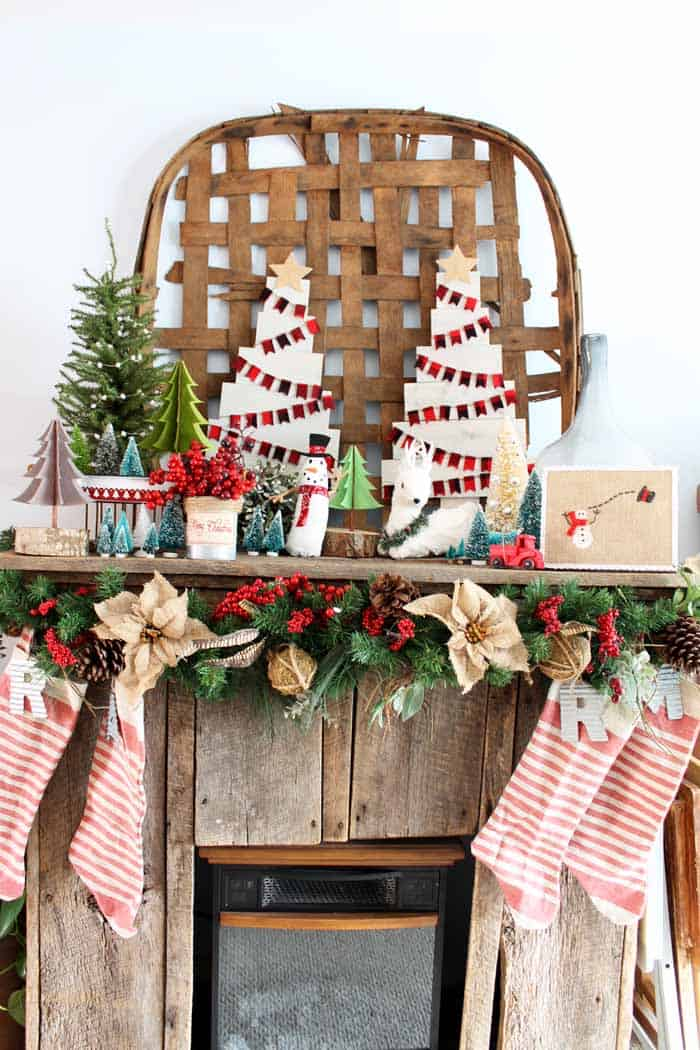 Farmhouse Christmas Decor a beautiful reclaimed wood mantel with DIY wood christmas trees, stockings and a bunch of christmas trees.