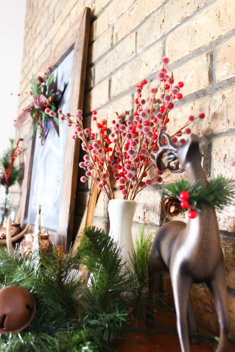 Mantel Decorations for Christmas, sign view of reindeer and berries in a pitcher with garland on a mantel