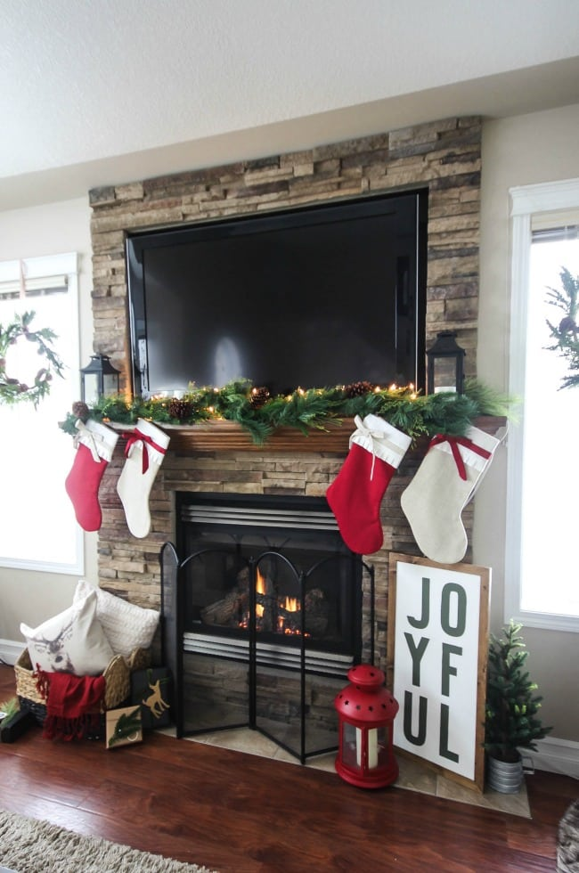 Mantel Decorations for Christmas, beautiful stacked stone fireplace, lighted garland and TV on mantel, red and white stockings and decor