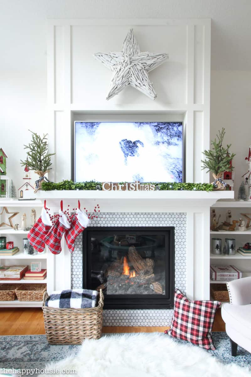Mantel Decorations for Christmas. A mantel with a tv above, use a pretty garland and plaid stockings