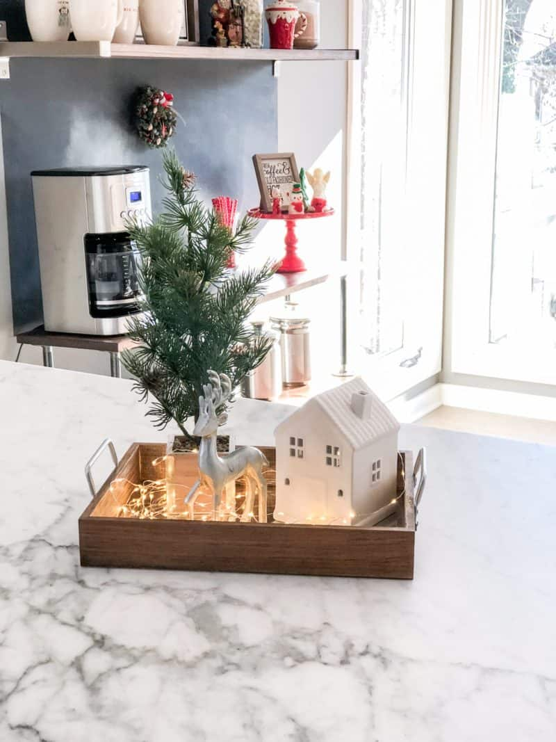 Christmas Kitchen Decorations in a tray, a house, reindeer, tree and fairy lights.
