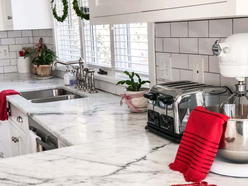 Marble Countertops, white subway tile and lots of red touches in my Christmas Kitchen Decorations.