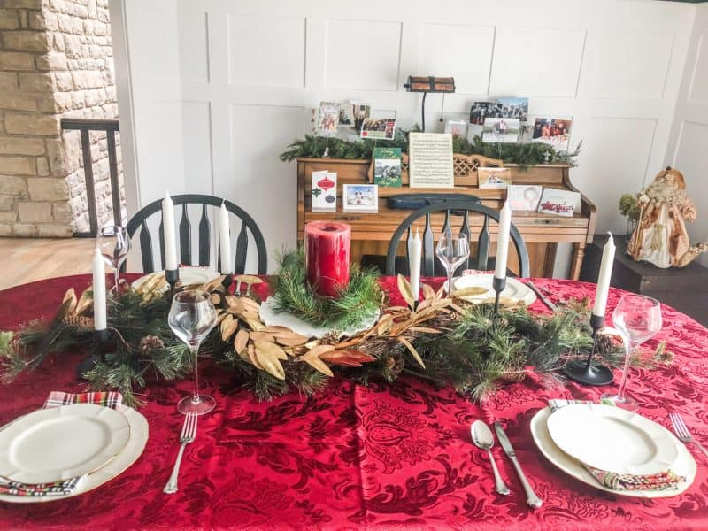 A Christmas Table Setting with a red table cloth and plaid napkins with neutral plates.