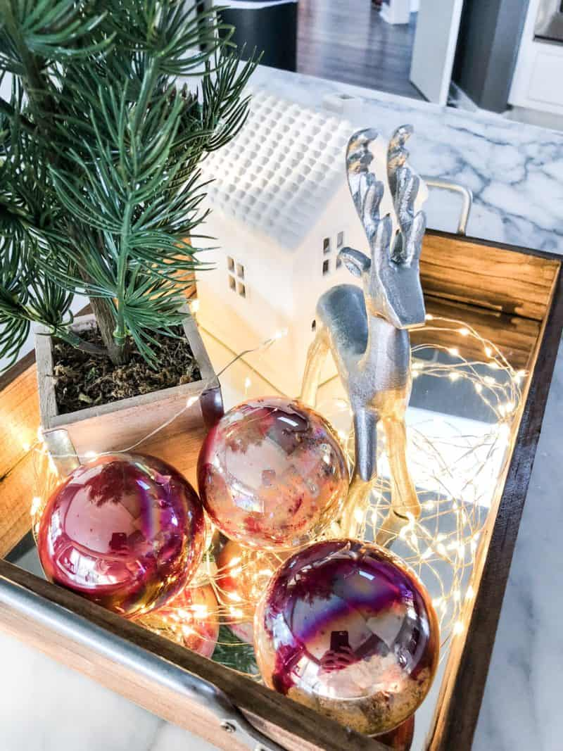 DIY marbled ornaments on a tray with other Christmas decor.
