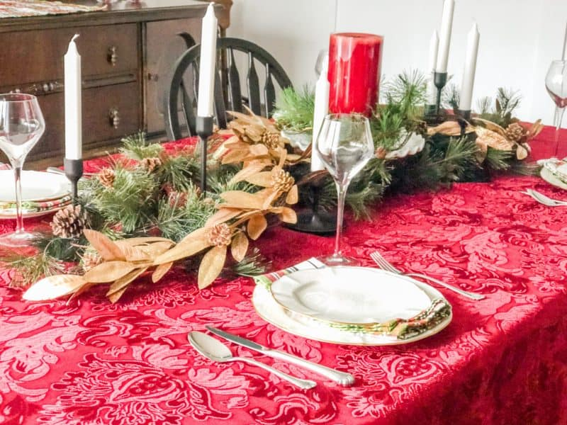 A Red table cloth with gold garland down the middle mixed in with a green garland.