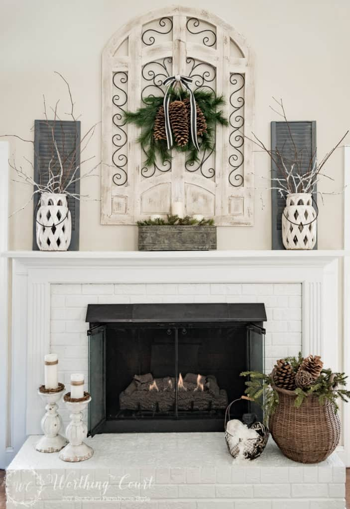 Mantle photo of pine cones, greenery and tree branches for Winter Decor.