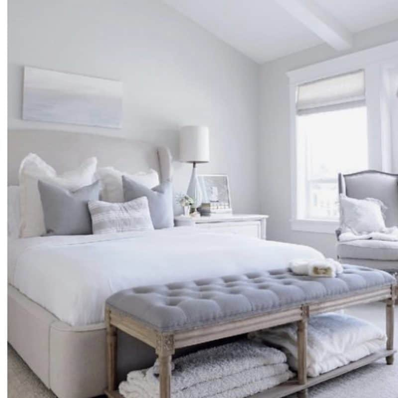 beige padded bed with a gray tufted bench. beautiful neutral colors in this room.