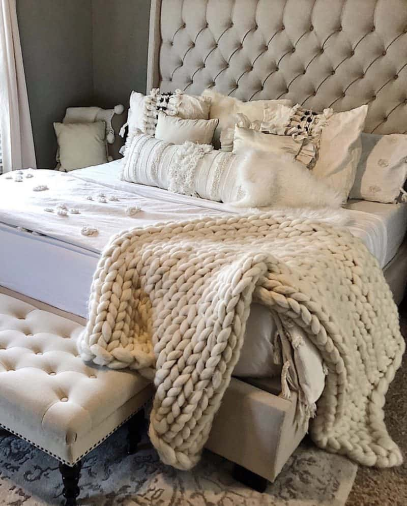 beige tufted headboard and beige tufted bench with a chunky knit blanket and textured pillows.