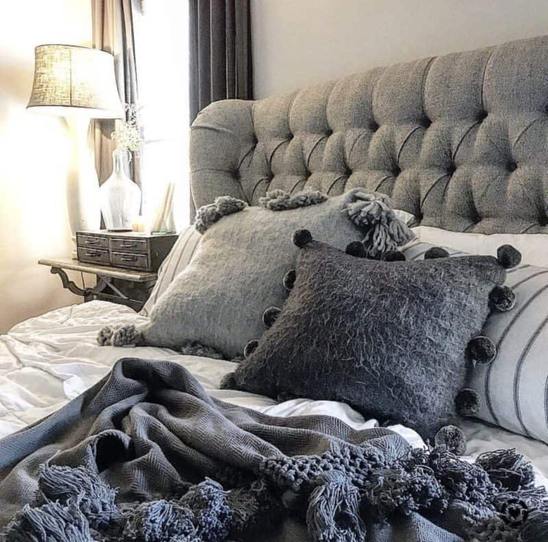 Gray bed with white bedding, throw pillows and a throw blanket.