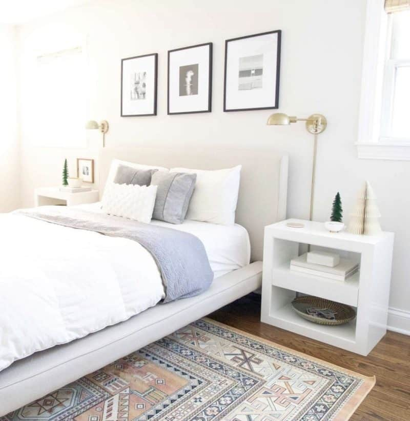 beige padded bed with white bedding and gray blanket. muted aztec patterned rug.