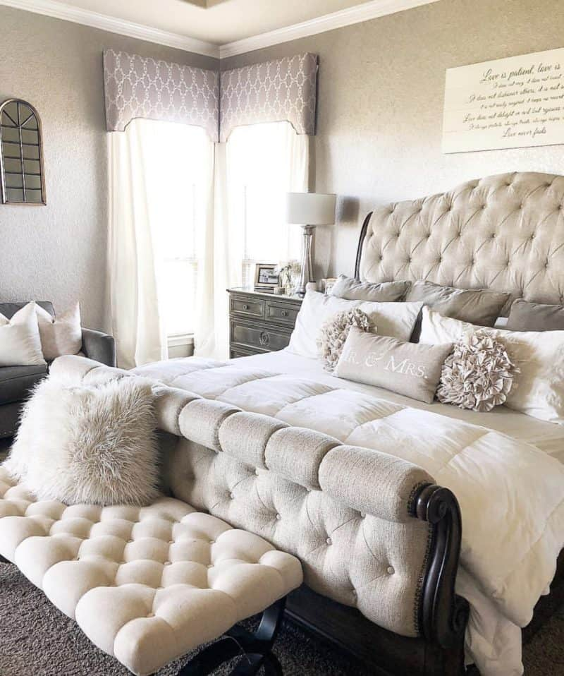 beige tufted bed with a beige tufted bench in front of it.