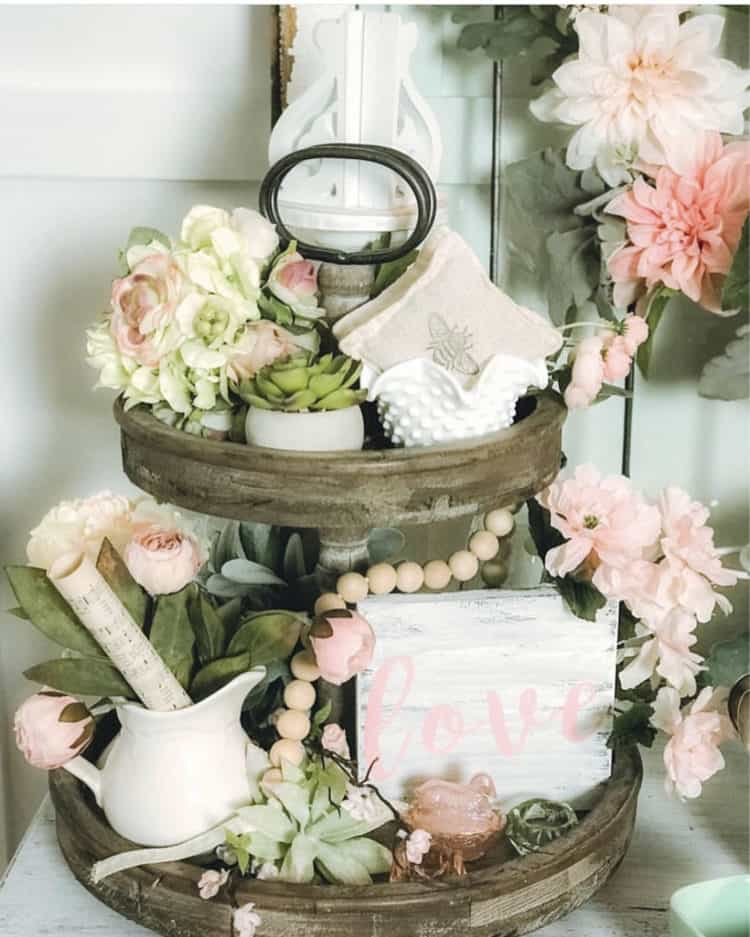 Tiered tray with soft pink flowers, a sign that says love and lots of greenery.