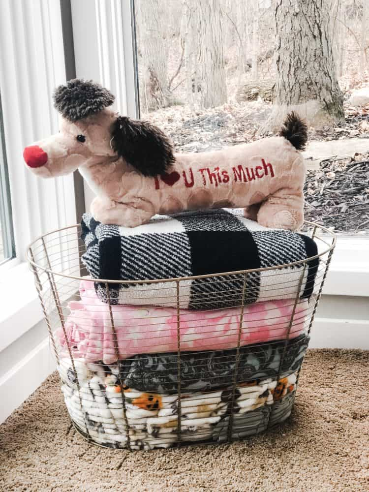 A Gold wire basket full of my daughters blankets with a stuffed animal on top.