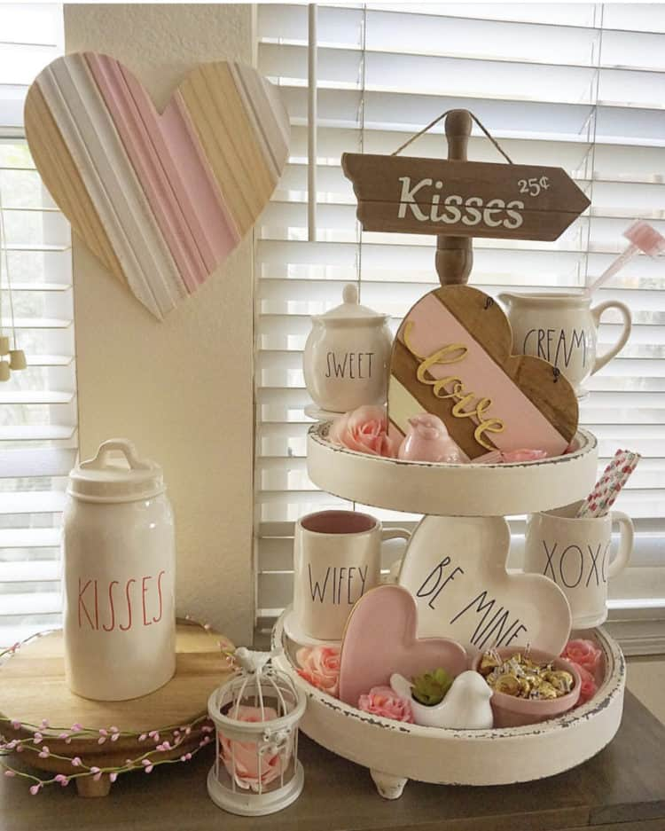 A tiered tray with Rae Dunn pottery saying Be mine, XOXO, wifey and kisses.