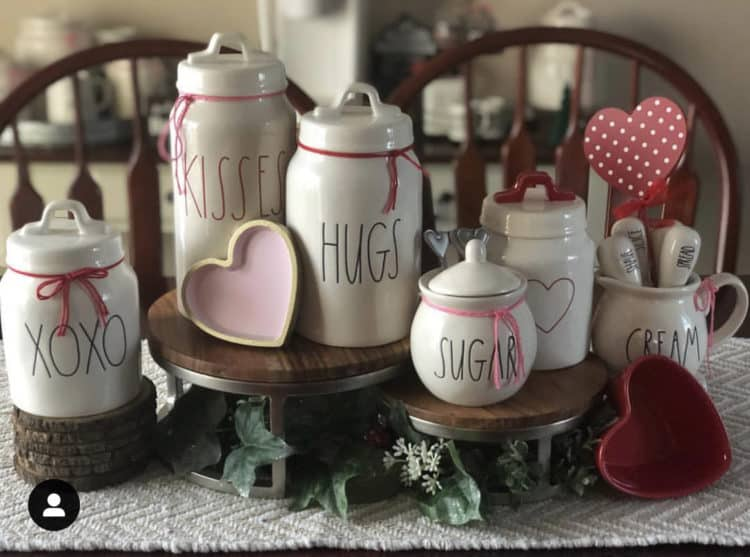 Pretty Rae Dunn canisters with love phrases and pink and red accents.