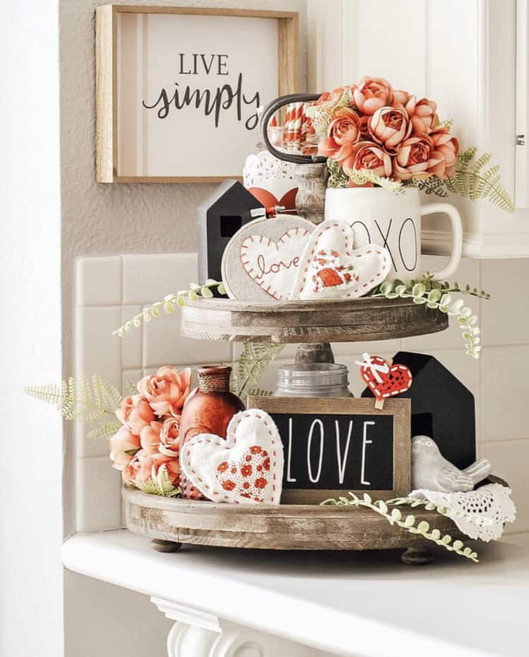 Tiered tray with coral accents. A couple farmhouse signs that say love and live simply.