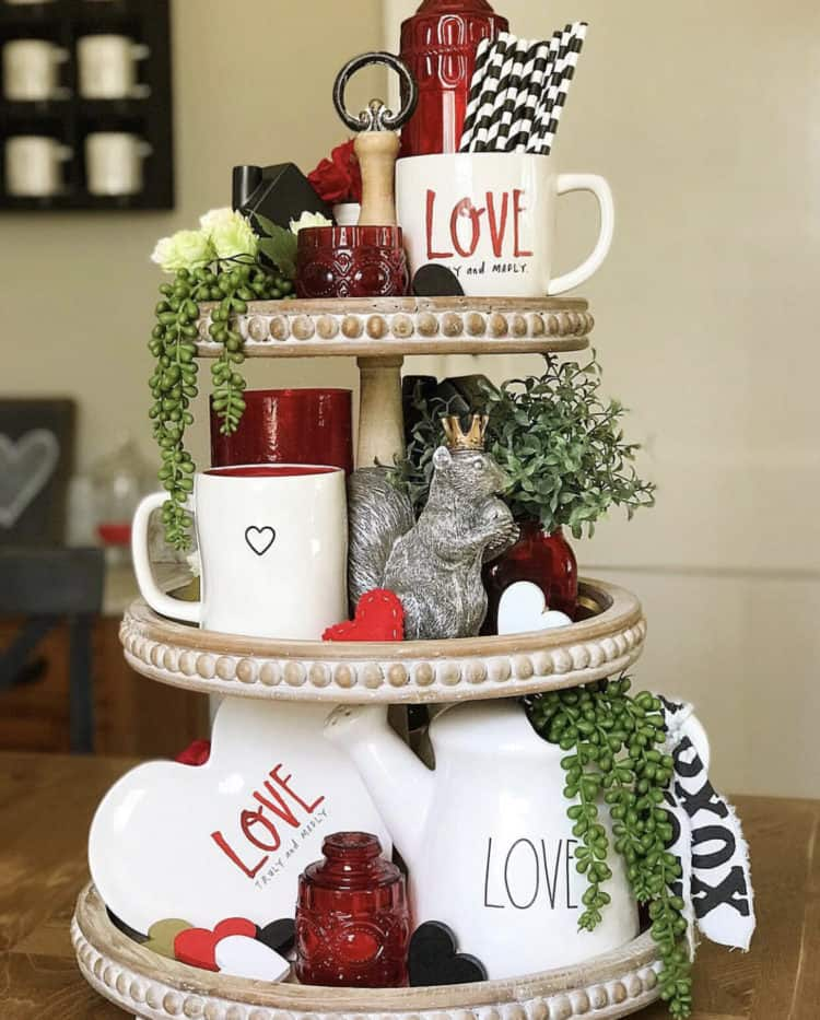 Tiered tray with love written on lots of pottery and some greenery with red accents.