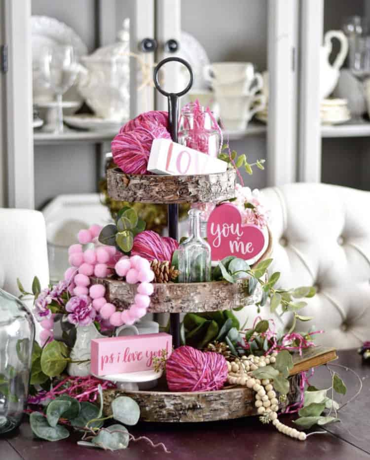 Tiered tray with pink accents and farmhouse signs saying love, you and me and ps I love you.