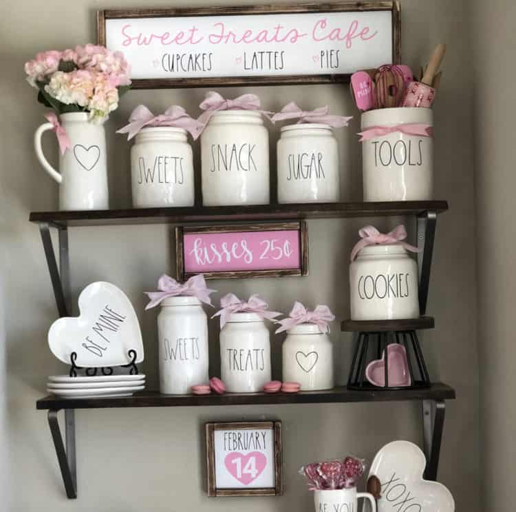 A display of Rae Dunn with pink accents and farmhouse signs.