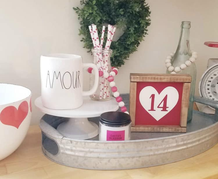 A metal tray with a farmhouse sign that has a heart and 14 in it. Also a Rae Dunn mug that says amour.