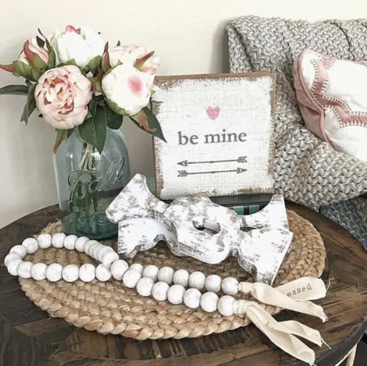 A farmhouse sign that says be mine with a heart and arrows on it.