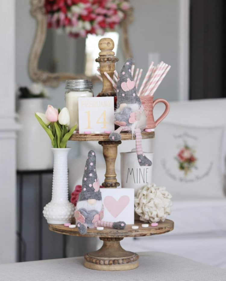 This tiered tray has a milk glass bottle with tulips in it, a couple gnomes with pink hearts on their hats and some bugs that are pink and white.