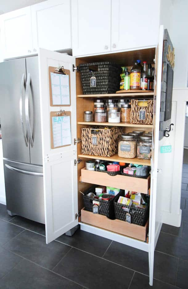 A pantry with baskets, glass jars with labels and pull out drawers.