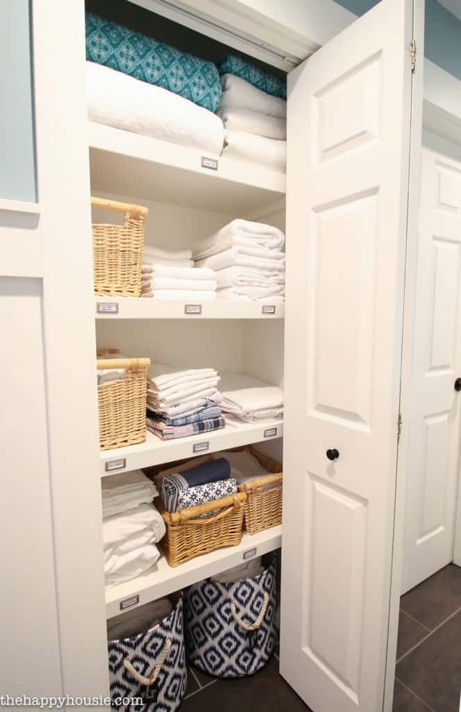 A linen closet with labels on the shelf so everyone knows where everything goes. Towels folded nicely and baskets to corral items.