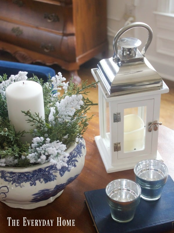 A beautiful vignette with white candles, flowers, and a white lantern.