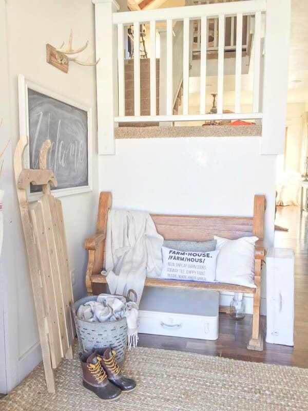 An entryway with white pillows, a white blanket and other neutral decor.