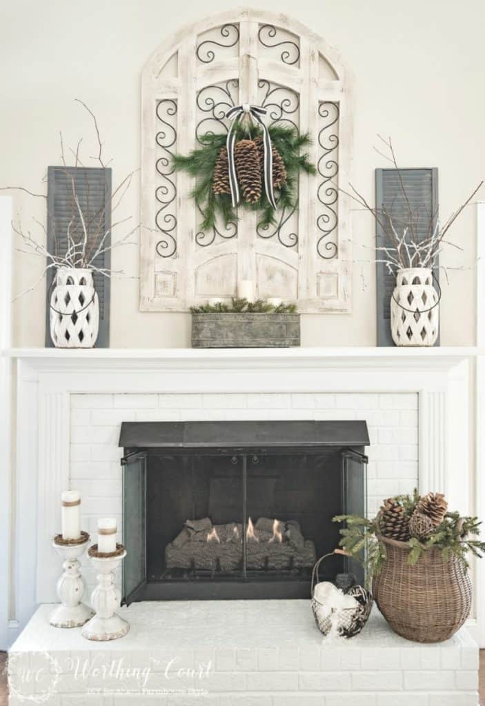 A beautiful mantel with white candlesticks and white candles, white wall decor and white vases.