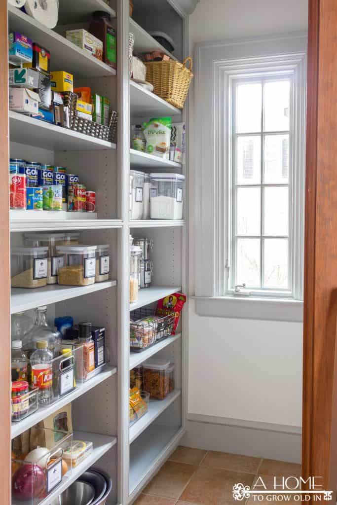 A large walk in pantry with glass jars neatly labelled and everything very organized.