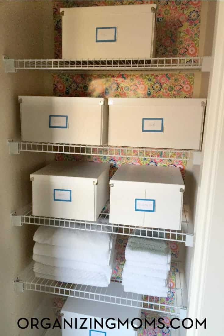 A linen closet with floral wallpaper on the back wall, storage boxes on shelves with labels and some white towels stacked neatly on the bottom shelf.