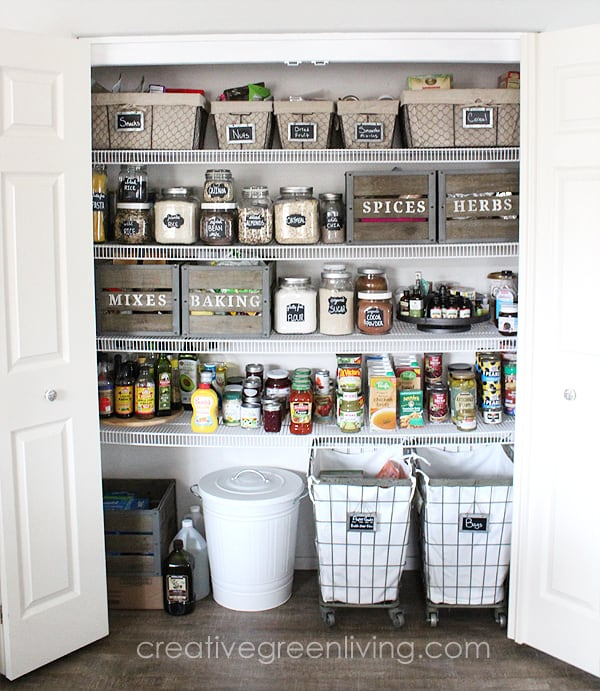 A pantry that is organized with glass jars with labels, baskets with labels and wood crates with labels.
