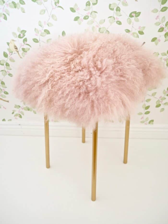 Ikea hack using a stool that was spray painted gold and adding a pillow to the top to make a pink fluffy cushion.