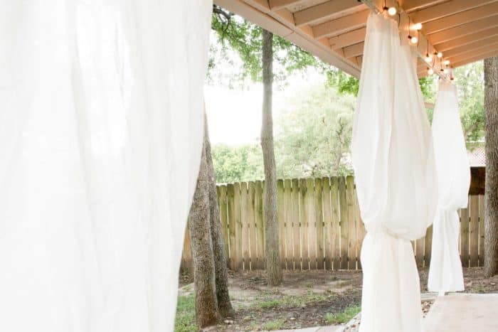 White curtains hanging from a cover patio.