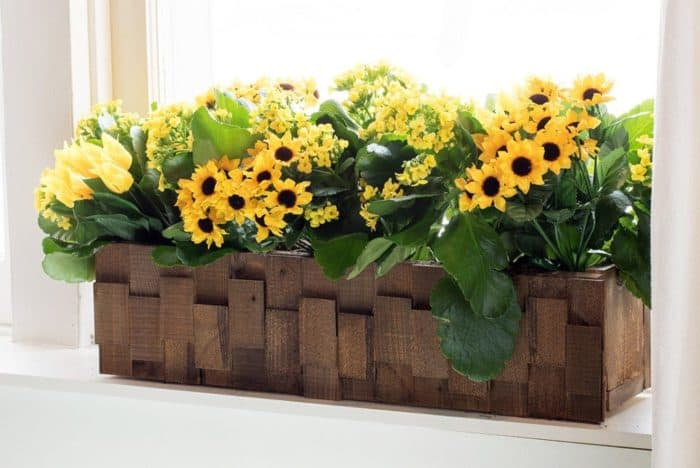 A rectangular box made of wood with pretty yellow plants in it.