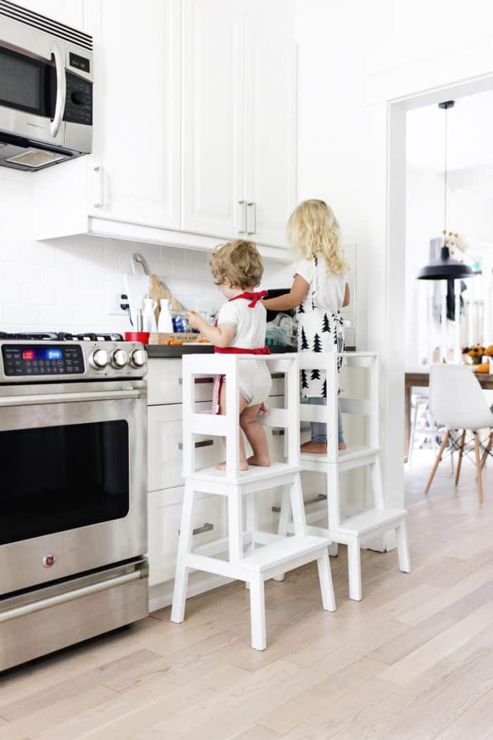 IKEA Hacks, two little girls standing on stools modified so they are safe working at the kitchen counter.