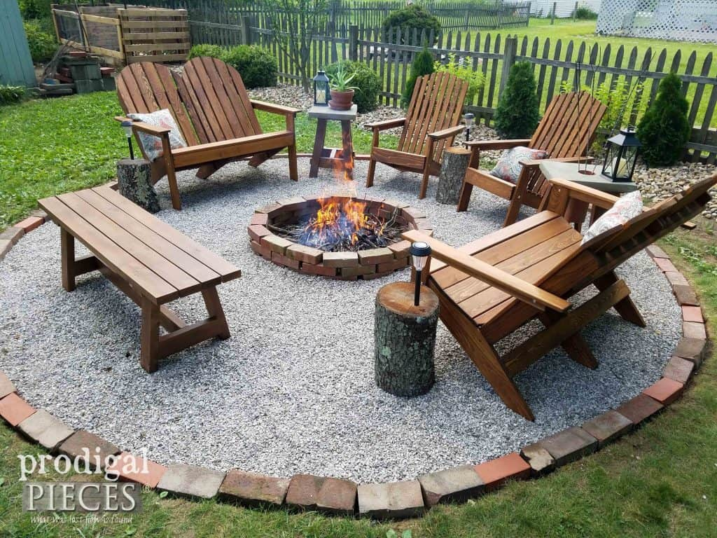 A fire pit with a gravel patio around it and lots of Adirondack chairs.