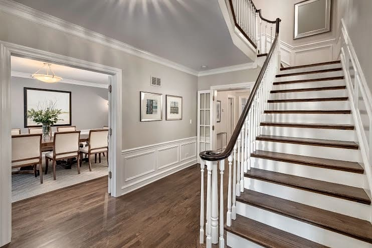 Edgecombe Gray Paint color in an entryway with a grand staircase and wainscotting.