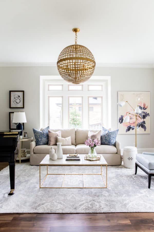 Classic Gray Greige Paint Color in a family room with a beige couch and a gold and marble coffee table on a gray rug.