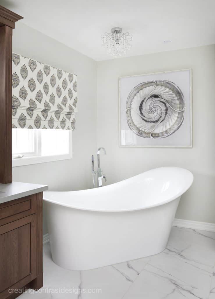 Gray Owl Greige Paint Color in a. bathroom with a gorgeous free standing bathtub.