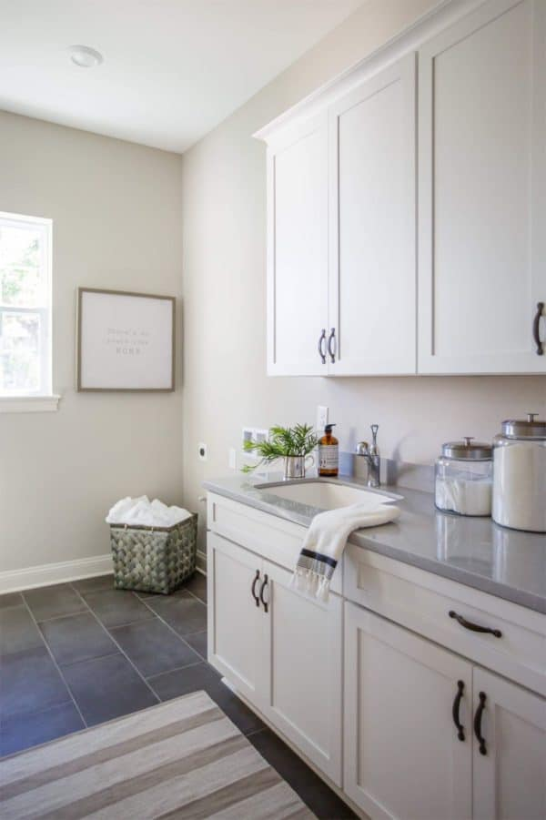 Worldly Gray Greige Paint Color in a Laundry Room with white cabinetry and gray slate tile floors.
