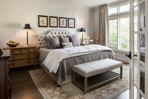 Useful Gray Greige Paint Colors in a family room with an upholstered headboard, tons of windows and gray bedding.