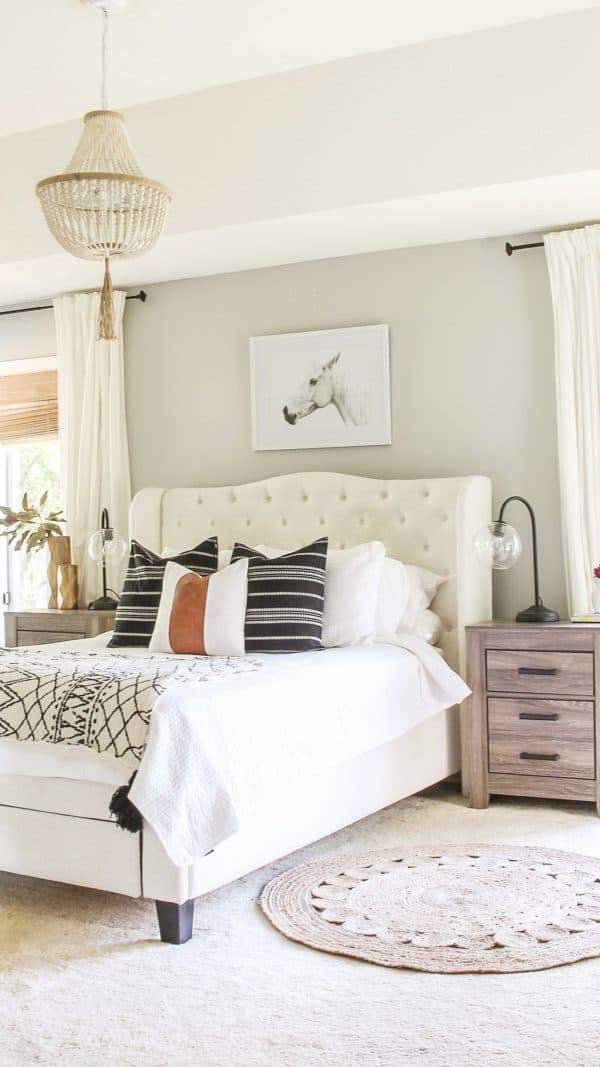 Repose Gray Greige Paint Color in a bedroom with a cream upholstered headboard and gray stained nightstands.