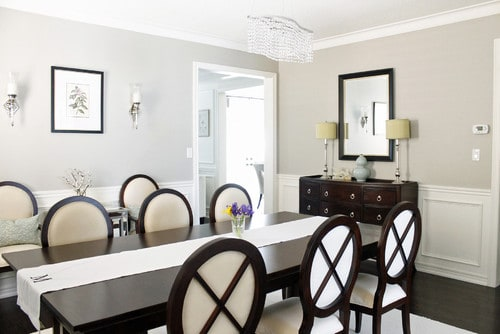Revere Pewter Greige Paint Color in a dining room with white wainscotting.