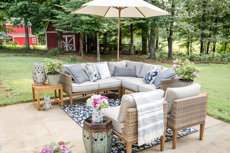 A sectional sofa and chairs on a patio with an umbrella and blue and white rug.